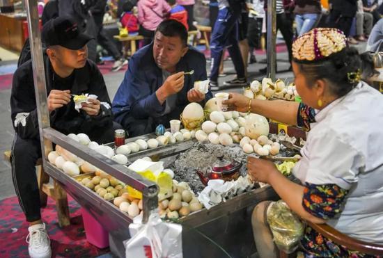 新疆和田夜市:游客品尝炭火烤蛋。中新社记者 刘新 摄