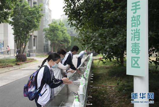 5月6日,武汉首批121所学校高三年级正式复学。在湖北省武昌实行中学,高三年级的门生入校后在手部消毒区洗手。 新华社记者 熊琦 摄