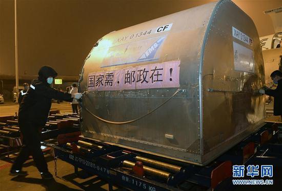 2月27日,第二批16台ECMO装备紧要运抵武汉,这是装卸员将装载ECMO装备的货仓从飞机上卸下。 新华社记者 李贺 摄