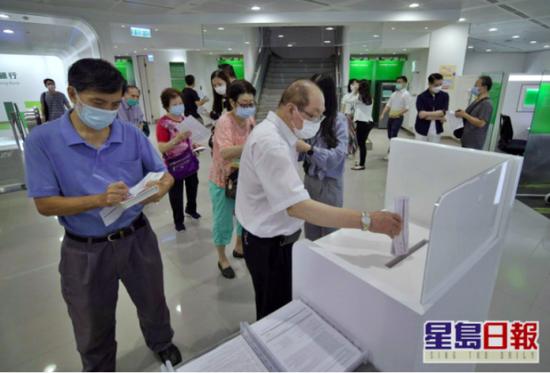 """不少市民今早前往银行排队交表。图源:香港""""星岛网"""""""