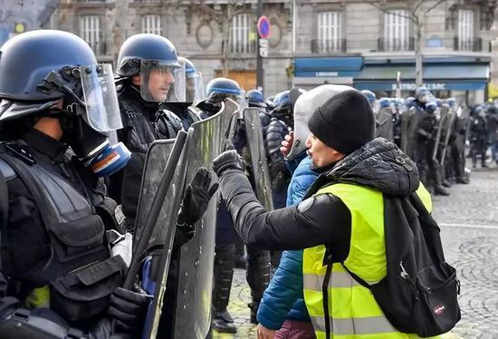 """这是2018年12月8日,""""黄马甲""""示威者在法国巴黎与警方对峙。新华社记者陈益宸摄"""
