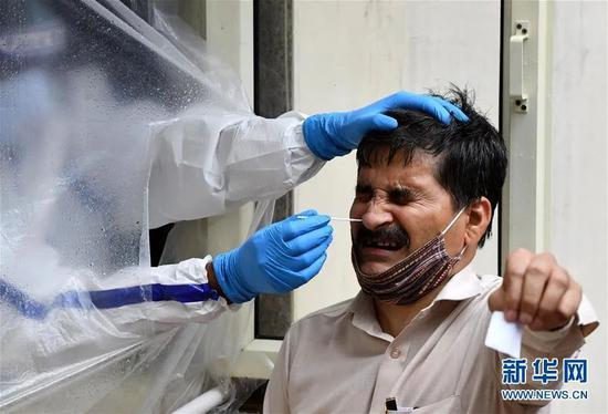 ▲资料图片:7月20日,医护人员为印度新德里居民进行新冠病毒检测采样。新华社发(帕塔·萨卡尔 摄)