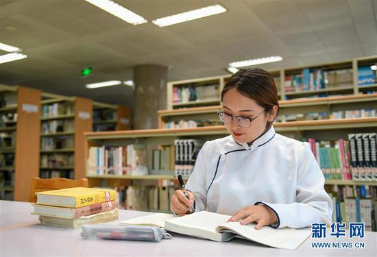 7月16日,内蒙古大学学生包高娃在图书馆学习。新华社记者 彭源 摄