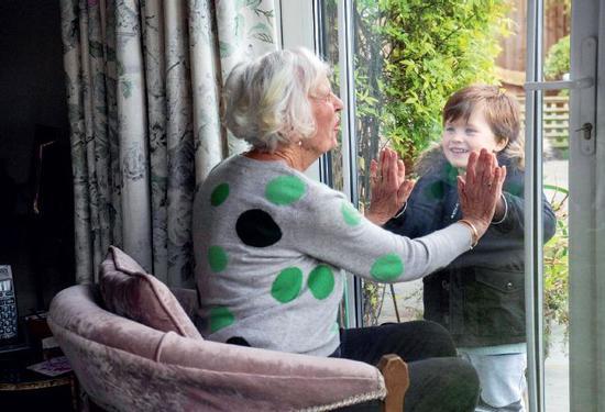 3月18日,在英国伦敦,一名4岁的小孩透过玻璃看望自我隔离中的曾祖母。