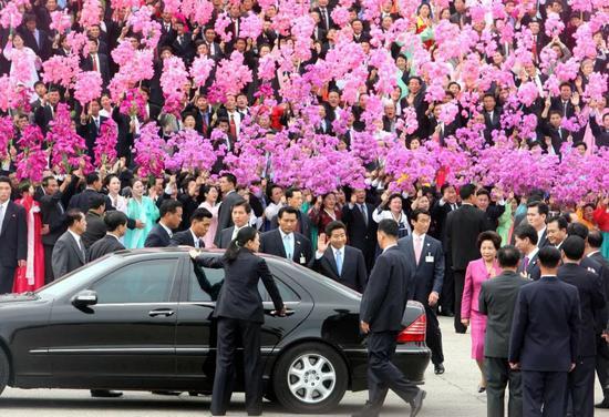"""2007年10月2日,在朝鲜首都平壤""""四・二五""""文化会馆前广场,朝鲜群众手持花束,欢迎来访的韩国总统卢武铉。(新华社发)"""
