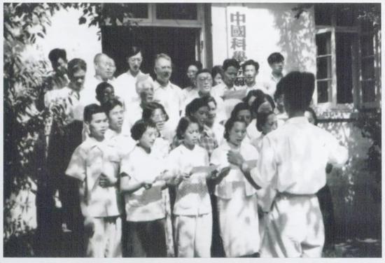 1958年,经济所工作人员在中关村办公楼前排练大合唱(后排左二:狄超白;后排左五:巫宝三;后排右三:汪敬虞;后排右一:桂世镛)。图片来源:经济所科研处