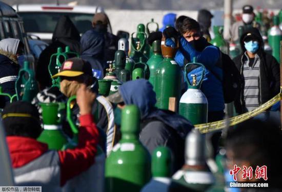 资料图:当地时间7月23日,秘鲁第二大城市阿雷基帕,新冠肺炎患者的家属排队给医用氧气瓶充电。