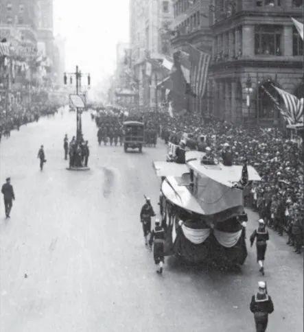 费城大游行挤满了街道两侧的人群,图中为士兵护卫的双翼飞机机身。