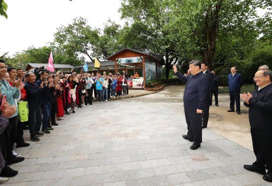 2021年4月26日下昼,习近平在桂林市象鼻山公园观察时,同旅客们亲热交换。
