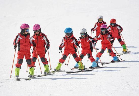 2018年2月7日,孩子们在江西省铜鼓县七星岭滑雪场进行滑雪接龙趣味训练。新华社记者万象摄