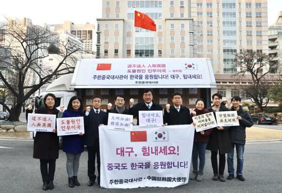 2月27日,在韩国首尔,中国驻韩国大使邢海明(中)与馆员一起为大邱加油。新华社发(中国驻韩国大使馆供图)