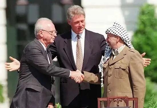 1993年,拉宾(左)阿拉法特(右)在克林顿(中)的见证下握手(图源:BBC)