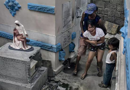 一位年輕的母親正在親手埋葬自己的兒子