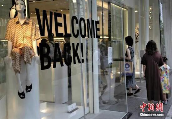 """当地时间6月6日,日本东京都发布新冠肺炎疫情""""东京警报""""后的首个周末,虽然当地已进入疫情恢复阶段,但各商场仍采取多种防疫措施严阵以待。图为东京街头某商店打出""""欢迎回来""""的标语。"""