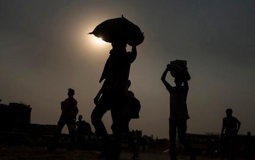 5月18日,在印度新德里郊区的加济阿巴德,头顶行李的农民工准备登上返乡大巴。新华社发(贾韦德·达尔摄)