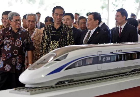 2016年1月21日,在印尼西爪哇省瓦利尼,印尼总统佐科(中)在雅万高铁开工仪式上观看高铁列车模型。新华社/美联