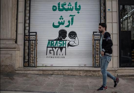为遏制伊朗国内新冠病毒疫情蔓延,伊朗卫生部呼吁民众近期减少聚会和观看体育赛事。图为2月26日,伊朗首都德黑兰,一名男子路过一家关闭的健身房