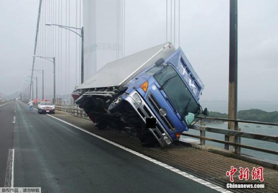 圖爲日本阪出,一輛卡車被大風吹翻。