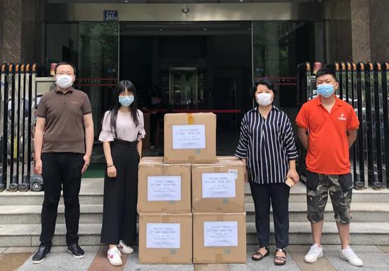 高静怡(左二)和同事们将写着祝福笔墨的标签贴在即将输送到孟加拉国的救济物资上。