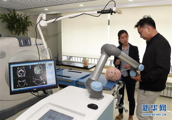 北京柏惠维康公司的工作人员在调试神经外科手术机器人(2018年5月10日摄)。北京柏惠维康公司研制的神经外科手术机器人在行业内占据领先地位。 新华社记者罗晓光摄