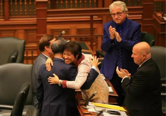 2017年10月26日,在加拿大多伦多,安大略省议会议员黄素梅(中)与同事拥抱庆祝动议获通过。新华社发(邹峥摄)