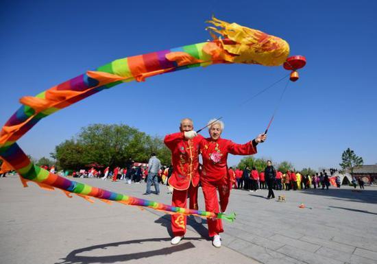 2018年4月7日,在山西运城永济市鹳雀楼景区,空竹爱好者在舞动空竹。新华社发(李向东 摄)