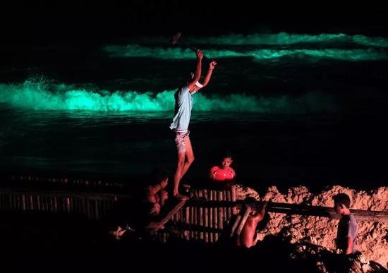 2011年6月10日,泰国普吉岛上,泰国和缅甸工人夜间在沙滩上打木桩,以阻止汹涌的海浪侵袭海边的餐馆。新华社/EPA欧新