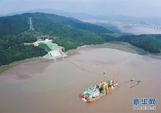 ▲最後一段海纜從施工船拖向終端站。(新華社)