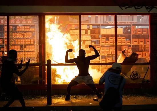 在商铺内放火的抗议者(图源:美联社)