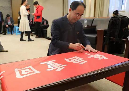 """杨柳青画社社长王勇在""""年画重回春节""""主题采风活动横幅上签名。"""