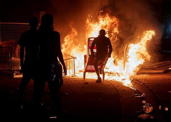 27日晚,明尼阿波利斯示威者焚烧购物车(路透社)