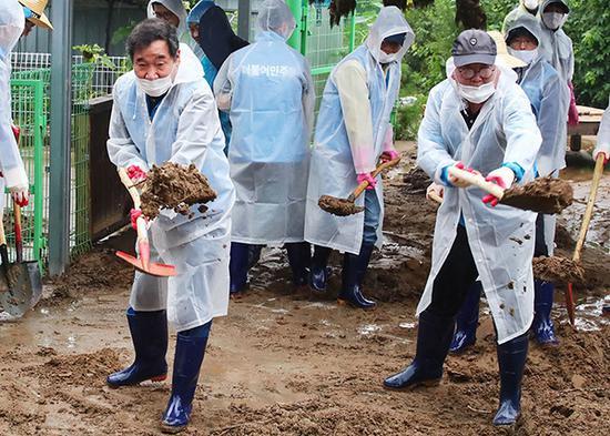 8月11日,韩国国务总理李洛渊等官员慰问灾民,帮忙铲土。人民视觉 图
