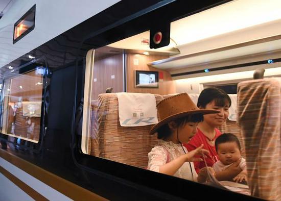 """乘客正在乘坐""""复兴号""""高铁列车。(新华社)"""