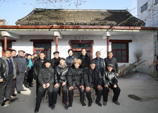 許家印和妻子丁玉梅回到太康縣高賢鄉聚臺崗村,和長輩、小時同伴在自家院子裏合影。