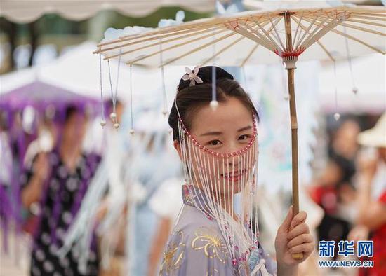 云南省昆明市,身着传统服饰的女孩手撑纸伞参加七夕节特别活动。