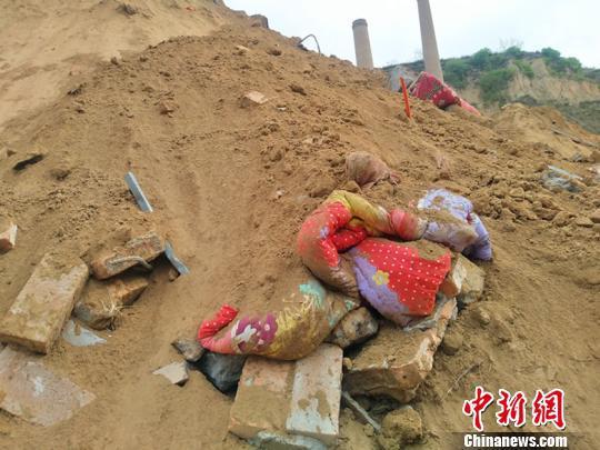 与黄土混合的衣服、被子、鞋子等物品夹杂在一片黄土废墟中。 刘小红 摄