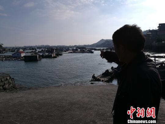58岁的肖车明站在码头上,手指向不远处的自家渔排,对今后的日子充满无奈。 陈龙山 摄