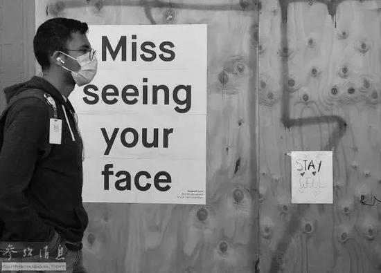 """▲4月1日,在旧金山,男子经过一张写有""""想念见到你的脸""""的海报。(法新社)"""
