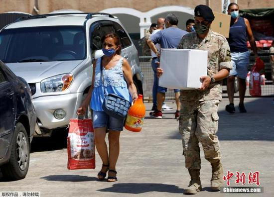 图为8月12日,黎巴嫩贝鲁特港口地区发生大爆炸后,一名妇女从军队领取分发的援助物资。
