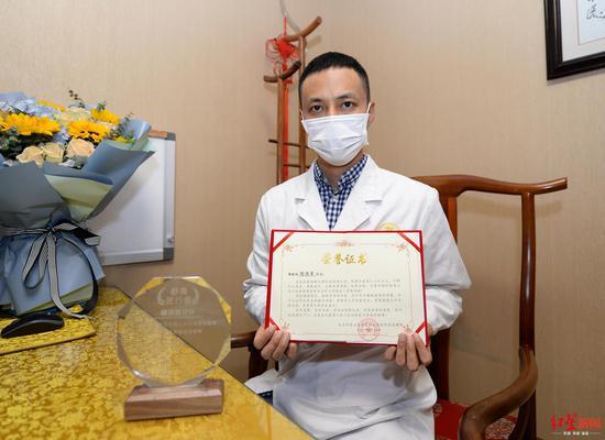 2020年4月17日,陈伟军向记者展示在武汉抗疫中得到的声誉证书