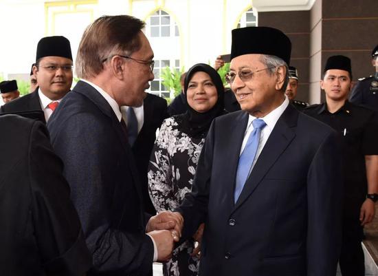 5月16日,在马来西亚首都吉隆坡,马来西亚总理马哈蒂尔(前右)与安瓦尔(前左)握手。新华社/路透