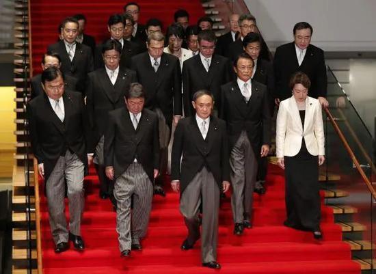▲9月16日,在日本东京首相官邸,日本首相菅义伟(前排中)率阁僚走下楼梯,准备合影。(新华社)