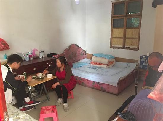 中午,胡仁荣一家在出租房里吃午饭。她的丈夫因行动不便,只能坐在靠墙的书桌边。