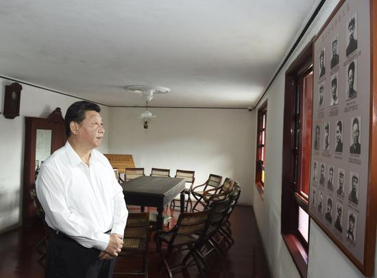 ↑2015年6月16日,习近平在观光遵义集会集会室时,蜜意注视墙上的遵义集会加入职员照片。