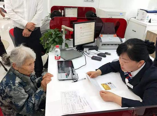 银行工作人员向马旭核对确认捐款数额