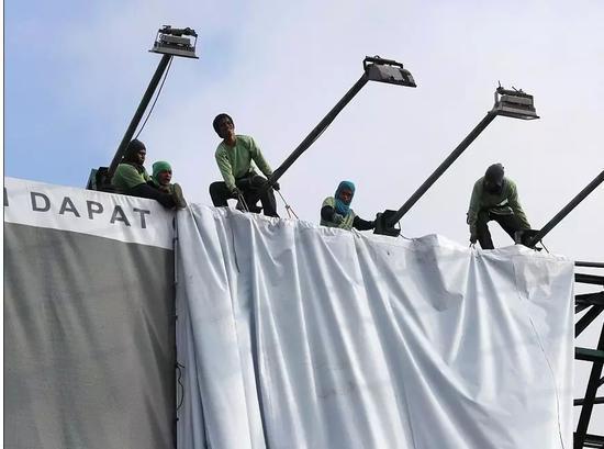 ▲菲律宾工人正在紧急拆除可能被吹走,造成危险的广告牌 图据《每日邮报》