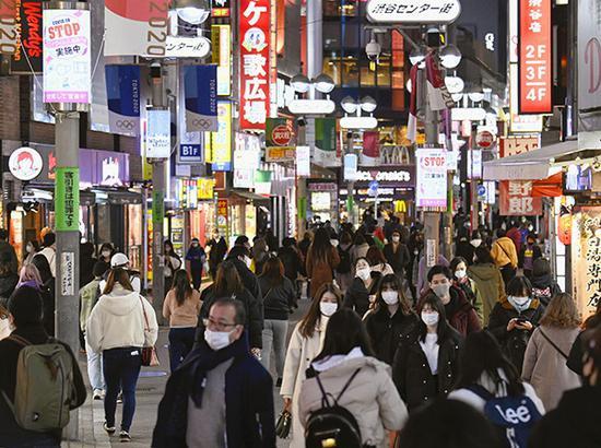 2021年1月5日,日本东京,市民佩带口罩出行。 视觉中国 图
