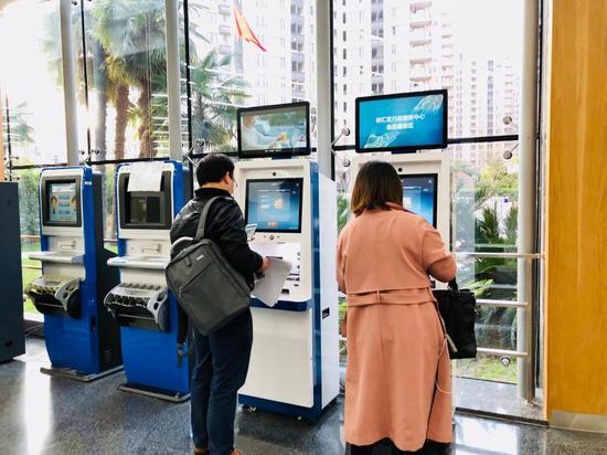 办事人员在徐汇行政服务中心大厅使用自助服务机。 舒抒 摄
