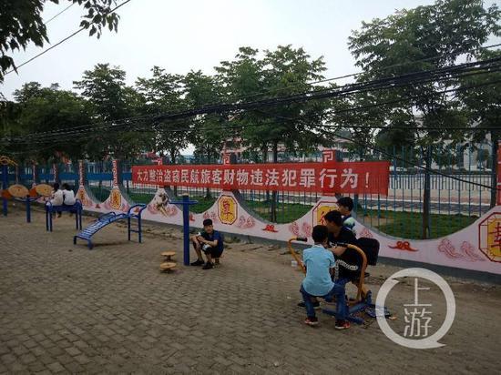 罗山县周党二中门口广场上的学生和打击飞机盗窃的标语。摄影/记者牛泰