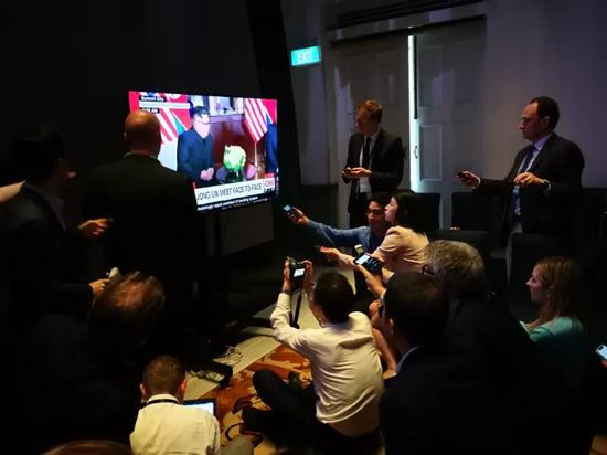 各国记者们围在新闻中心电视前记录金特会的历史时刻